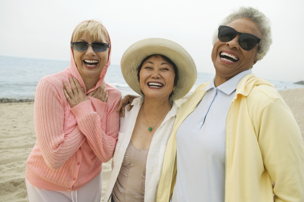 diverse-senior-women-laughing-on-beach